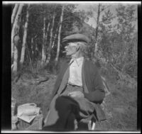 Abraham Whitaker smokes a cigar and sits on a chair while camping at Convict Lake, Mammoth Lakes vicinity, 1929