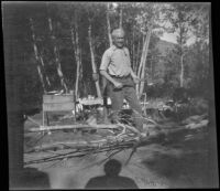 Forrest Whitaker holds a hatchet and smokes a pipe while camping at Convict Lake, Mammoth Lakes vicinity, 1929