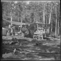 Mertie West, Agnes Whitaker, and Forrest Whitaker next to a temporary camping kitchen at Convict Lake, Mammoth Lakes vicinity, 1929
