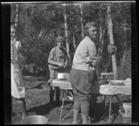 Mertie West, Edith Shaw, and Agnes Whitaker stand around a table at Convict Lake, Mammoth Lakes vicinity, 1929