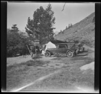 Abraham Whitaker stands by H. H. West and family's campsite and cars at Twin Lakes, Bridgeport vicinity, 1929
