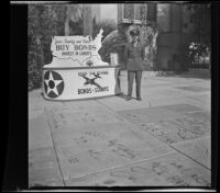Lynn West poses by the handprints at Grauman's Chinese Theatre next to a display for war bonds, Los Angeles, 1942