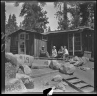 Neil Wells, Mertie West, Frances West Wells and H. H. West, Jr. sit on the back porch of the cabin, Big Bear Lake, 1932