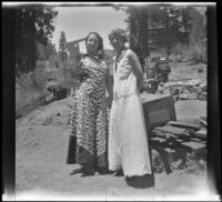 Frances West Wells and Mertie Whitaker West stand in front of a woodpile outside a cabin, Big Bear, 1932
