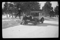 H. H. West, H. H. West, Jr., Mertie West and Frances West Wells sit around H. H. West's Buick on a snowy road, Big Bear, 1932