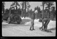 Neil Wells hitches a sled to H. H. West's Buick as Mertie West watches him, Big Bear, 1932