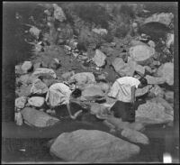 Elizabeth West and Frances West scramble across rocks, Sunland-Tujunga vicinity, 1912