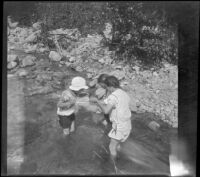Frances Cline, Frances West and Elizabeth West wade in Big Tujunga Creek as they peer at something held in a cloth, Sunland-Tujunga vicinity, 1912