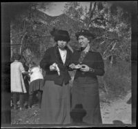 Mrs. H. H. West (Mary A.) and Bessie McGee Velzy pose for a photograph while they eat, Sunland-Tujunga vicinity, 1912