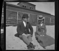 Ora Prickett and Mertie Whitaker sit in the sand in front of the North Beach bathhouse, Santa Monica, 1901