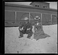 H. H. West and Mertie Whitaker sit in the sand in front of the North Beach bathhouse, Santa Monica, 1901