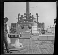 A man peeks at the camera while standing in front of gun turrets aboard a battleship off the coast, Santa Monica, about 1900