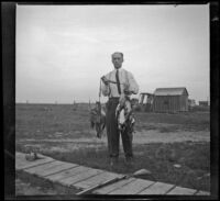 Carl Salbach poses with ducks killed during a hunt, Orange County vicinity, 1912