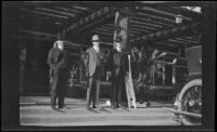 Three men stand on the steps of the Pebble Beach Lodge, Pebble Beach, about 1920