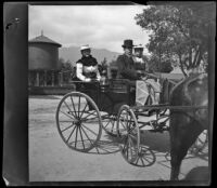 Louise Ambrose, H. H. West and Nella West sit in a carriage near the Lamanda Park water tank, Pasadena, 1899