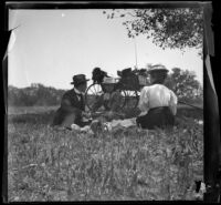 Charlie Rucher, Nella West and Louise Ambrose sit in the grass near Devils Gate, Pasadena, 1899