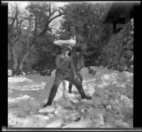 Mertie West helps H. H. West, Jr. balance a block of ice on his head, Redlands vicinity, about 1930