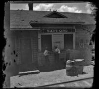 Three men stand at the Safford train station ticketing window, Safford, 1895