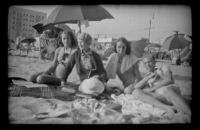 Margaret Deming, Mertie West, Jane Deming and H. H. West, Jr. lounge on the beach, Hermosa Beach, 1937