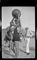 Salesman Burt holds a beach ball above his head, Hermosa Beach, about 1932