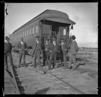 Several Southern Pacific Railroad employees pose in front of a train car, Salton Sea vicinity, about 1899