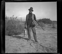 Webster Brain poses with rabbits and quails, Irwindale, about 1900