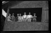 Worm's-eye view group portrait of members of the West, Whitaker, Shaw, Prickett and Witherby families standing on a porch, Manhattan Beach, about 1930