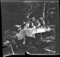 Mertie West, Agnes Whitaker and Forrest Whitaker dine at a picnic table at Soper's Ranch, Ojai vicinity, about 1927