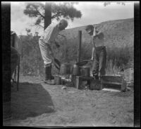 H. H. West and H. H. West Jr. at a camping stove, Inyo County vicinity, about 1930