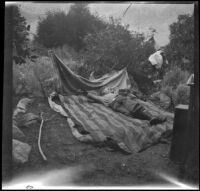 H. H. West Jr. lying on a bed during a camping trip, Inyo County vicinity, about 1930