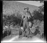 H. H. West Jr. holding fish and fishing gear, Inyo County vicinity, about 1930