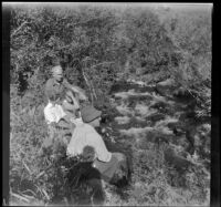 Forrest and Agnes Whitaker, Mertie West, and William Shaw sit by Pine Creek, Inyo County vicinity, about 1930
