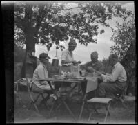 Mertie West stands at a table as Agnes Whitaker, Forrest Whitaker, and William Shaw eat breakfast at a campsite, Inyo County vicinity, about 1930