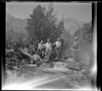 William Shaw, Mertie West, Agnes and Forrest Whitaker stand on rocks in Pine Creek while H. H. West Jr. sits in front, Inyo County vicinity, about 1930