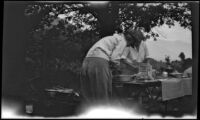 Agnes Whitaker and Mertie West prepare food at a table in a campsite, Inyo County vicinity, about 1930