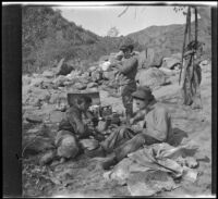 Winnie Scott, Cleo Swain and Mills Helen eating lunch near an outcrop of rocks, Los Padres National Forest vicinity, about 1917