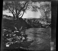 Cleo Swain washing kettles on the bank of Piru Creek, Los Padres National Forest vicinity, about 1917