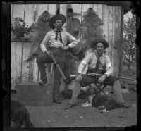 H. H. West and Bim Smith posing with their guns in front of animal pelts, Pomona, about 1895