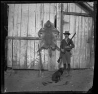 Ed Smith posing with a rifle, dog and a coyote pelt, Pomona, about 1895