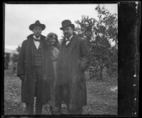 Bim Smith, Pearl Smith and Frank Baynham posing in an orange orchard, Pomona, about 1895