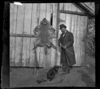Frank Baynham posing with a rifle, dog and an animal pelt, Pomona, about 1895