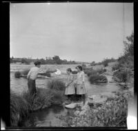 "William ""Babe"" Bystle holds his hat out to Frances and Elizabeth West as they stand in the Sacramento River, Redding vicinity, about 1914"
