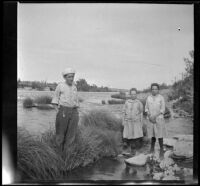 """William """"Babe"""" Bystle and Frances and Elizabeth West stand in the Sacramento River, Redding vicinity, about 1914"""