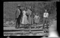 Wilson West, Mertie West, Eleanor West, Richard West and H. H. West, Jr. posing atop wood planks, Redlands vicinity, 1932
