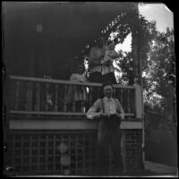 Frank Miller poses in front of his house as his family stands on the porch above, Red Oak, 1900