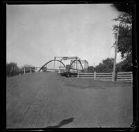 Iron bridge with dirt road and wooden fences, Red Oak, 1900