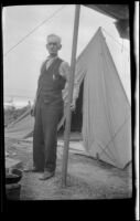 Abraham Whitaker standing in front of a tent near Rincon Point, Carpinteria vicinity, about 1924