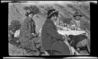 Edith Shaw, Mertie Whitaker and Josie Shaw dining at a table on the beach, Carpinteria vicinity, about 1924