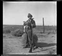H. H. West, Jr. posing with a gun and a rabbit, Rosamond vicinity, about 1930