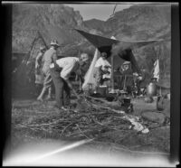 William Shaw chops wood while others gather at their campsite near Rush Creek, Mono County vicinity, 1929